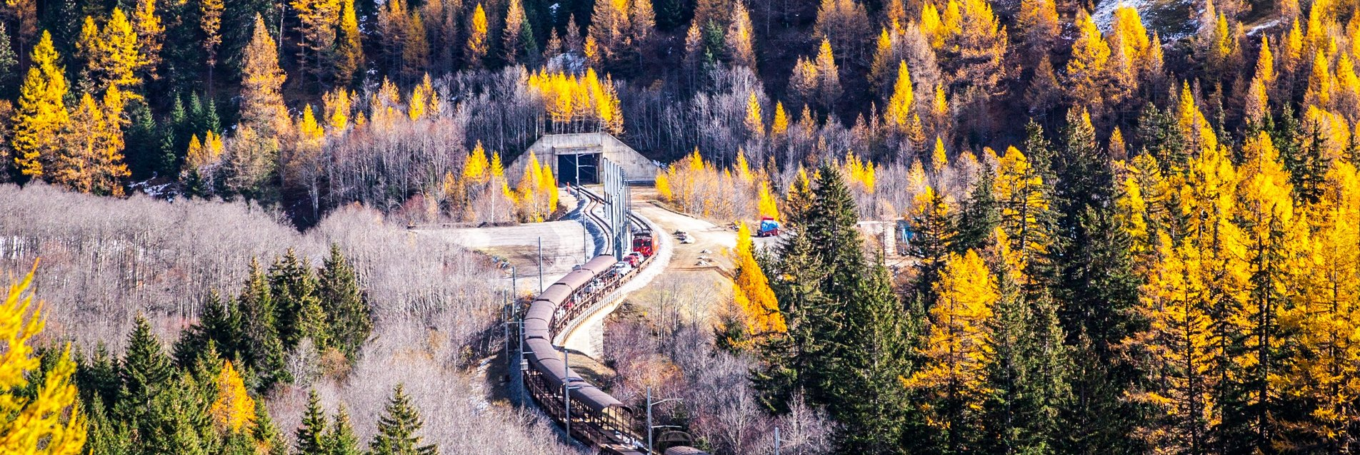 Autozug vor dem Furkatunnelportal im Herbst